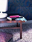 A white table lamp on a wooden side table on a fluffy lilac rug