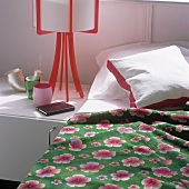A bed with a floral patterned quilt and a table lamp with a red plastic base on a bedside table