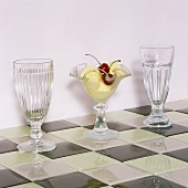 Various retro-style stemmed glasses, one filled with dessert on chessboard patterned tiles