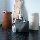 A shopping bag and coloured container in a mixture of materials and styles in front of an old fashioned ironing board