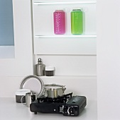 Coloured containers on a shelf above a pot on a single gas hob