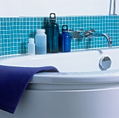 Detail of a bath tub with blue containers against blue wall tiles