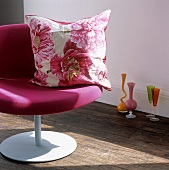 A floral patterned cushion on a pink armchair and coloured vases and stemmed glasses on the floor