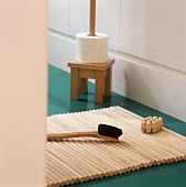 A brush on a wooden mat and a toilet roll holder