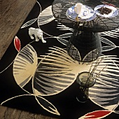 A coffee table, a floor vase and an animal figurine on a large black, patterned rug