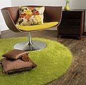 A wooden swivel chair on a round green rug