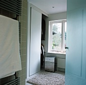 A heated towel rail next to a door in a changing room