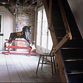 A rocking horse and a flight of wooden steps in an anteroom