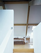 A view between a partition wall and a balustrade wall onto a bed in a converted attic room