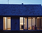 A simple detached house with terrace windows and a view into an illuminated bedroom