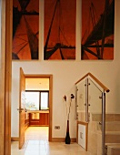 A minimalistic anteroom with steps and a modern triptych above an open kitchen door
