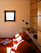Orange cushions on a bed under a small window and bedside lamps on a wooden shelf