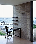 A simple study corner against a concrete wall and a glass facade with a view of the sea