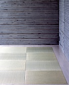 A corner of a room with exposed concrete walls and tatami mats on the floor