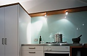 A white, modern kitchen with a glass splashback and spotlights built into the underside of a wooden shelf