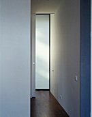 A minimalistic, white-painted hallway with parquet flooring