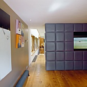 A television built into an upholstered partition wall with a view down a long corridor