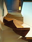 A modern spiral staircase with wooden steps and a glass balustrade