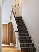 Staircase with striped runner and white turned balusters in modern foyer