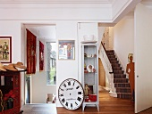 Collectors' items in foyer of renovated villa with view of stairs through open doorway
