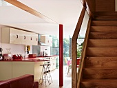 Simple wooden staircase next to open-plan kitchen with white cupboard fronts and a red painted metal pillar
