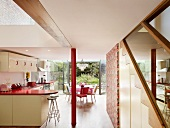 Open-plan kitchen and red painted pillar in front of dining area and open terrace window