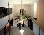 Open-plan, double-height foyer with pendant lamps and parked retro scooter