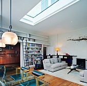 Living-dining room with skylight and light grey sofa set in front of fireplace