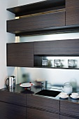 Dark wood shelving in front of glass wall in designer kitchen