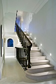 Traditional stairwell with stone stairs and black wrought iron balustrade
