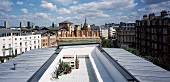 Elongate roof terrace between metal roofs with view of an English cityscape