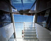 Reflections and blue sky seen through transparent roof terrace floor