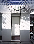 Pattern of light and shade on white wall through wire mesh floor above