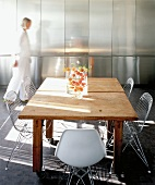 Blurred woman in front of reflective stainless steel fitted cupboards in sunny dining area with 50s-style wire mesh chairs