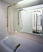 Bathroom seen in mirror over bathtub with designer tap fittings