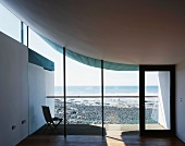 Empty living room with view of neighbouring beach through glass facade under concrete roof curving up as if floating on one side