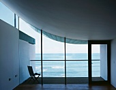 Empty room with view of terrace with chair and sea through glass facade under concrete sail curving up on one side