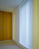Ceiling-height, smooth, wooden double doors next to windows with vertical louver blinds
