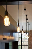 Pendant lamps with large, teardrop-shaped light bulbs in a high-ceilinged room with traditional factory windows