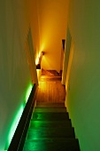 Walls of narrow, winding stairway with landing illuminated in different colours by indirect handrail lights behind wooden cladding