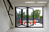 View through half-opened folding window onto roof terrace with two orange plastic chairs