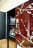 Reflection of living room in glossy, red-brown door of half-opened drinks cabinet with pattern of blossoming branches