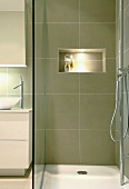 Shallow shower base with glass divider and illuminated niche serving as a shelf