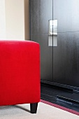 Red upholstered stool in front of reflections in handle elements of black, modern wooden cupboard