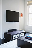 Small, abstract painting and wall-mounted flat screen TV above black audio cabinet