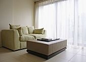 Upholstered sofa with soft cushions and cubist coffee table on a tiled floor in front of a wide window