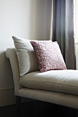 Scatter cushion with red leaf motif on white chaise longue with cushioned upholstery
