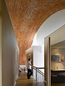 Top floor of residential building with expansive barrel vault above inserted cubic rooms in a corridor with stairwell