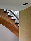 Arched stairs made of narrow bricks with wooden treads and balusters of randomly woven rope