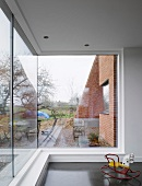 Small, colourful rocking horse in front of large corner window with view of a garden and brick walls